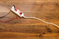 Voltaje de la medida en zócalo eléctrico con el multímetro fotos de archivo