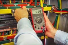 Voltaje eléctrico de las medidas del ingeniero con el primer del multímetro el electricista profesional mide voltaje con el proba Foto de archivo