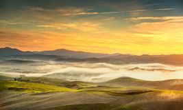 Volterra foggy panorama, rolling hills and green fields on sunse Stock Photography