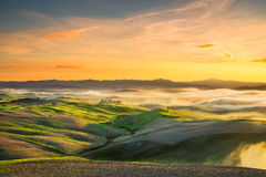 Volterra foggy panorama, rolling hills and green fields on sunset. Tuscany, Italy royalty free stock photos