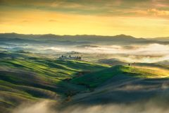 Volterra foggy panorama, rolling hills and green fields on sunse. T. Tuscany Italy, Europe Stock Image
