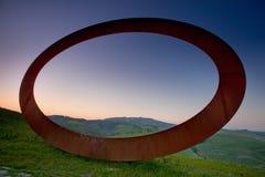 Volterra Tuscany, Italien - Volterra medeltida stad, de scultorMauro Staccioli arbetena som installeras i 2009 för utställning Arkivfoto