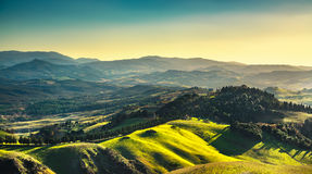 Volterra winter panorama, rolling hills and green fields on suns Stock Image