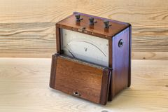 Voltmeter vintage with wooden cover. On a wooden plane.This instrument of the 50s, was used to measure the voltage of electricity royalty free stock images