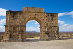 Volubilis Triumphal arch, Morocco. The Triumphal arch of Volubilis with the Moroccan landscape as background. Volubilis was an ancient roman village and its Stock Photography