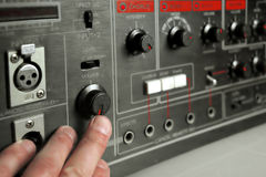 Volume Control. DJ hand pushing volume up on studio equipment, indoor shot with selective focus Stock Photography