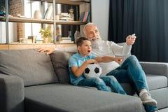 Volume croissant de grand-père sur le poste TV tout en observant le football Photographie stock libre de droits