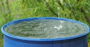 Volume de água da parte superior em um grande tambor azul na jarda video estoque