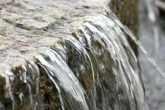 Volume de água sobre a borda de pedra da fonte velha da cidade Imagens de Stock Royalty Free