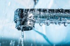 Volume de água de um close-up macro cromado moderno do torneira da torneira de água imagem de stock royalty free