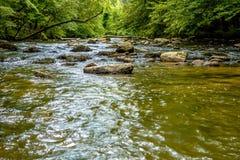 Volume de água largo do rio através das montanhas de cume azul Fotografia de Stock