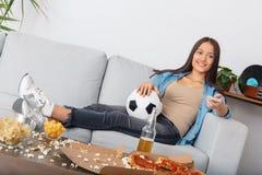 Volume em mudança de observação do fósforo do aficionado desportivo da jovem mulher com controlador remoto foto de stock