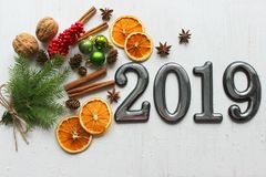 Date 2019 on white wooden background, fir branches, cinnamon sticks and dried orange slices, bokeh effect. 2019 New year stock photography