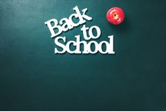 Volume White Letters Back To School Apple Concept. Volume White Letters Back To School with Apple Concept Stationery on Green Background Copy Space Top View Flat Stock Photo