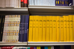 Volumes of books on bookshelf in library Stock Images