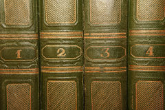 Volumes of old books with gold lettering on the cover. Volumes of old books with gold lettering on the green cover Stock Images