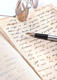 Volumes, spectacles, and a fountain pen. Close up photo Royalty Free Stock Image