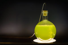 Volumetric flask with green liquid chemical experiment. Volumetric flask with green liquid in experiment in dark room laboratory, chemical reaction, destillation Stock Photo