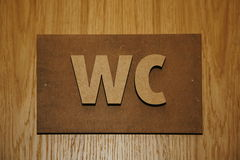 Volumetric plaque on wooden doors toilet rooms - Water Closet - WC. Stock Image