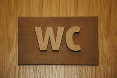 Volumetrische Plakette auf Holztürtoilettenräumen - WC - WC Stockbild