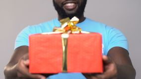 Voluntário afro-americano de sorriso que guarda o giftbox do cartão, caridade do auxílio filme
