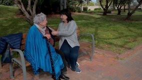 Volunt?rio f?mea e conversa idosa da mulher que sentam-se em um banco em um parque da cidade vídeos de arquivo