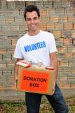 Voluntário feliz com a caixa da doação do alimento Fotografia de Stock Royalty Free