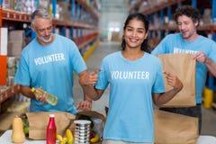 Voluntário feliz que mostra seu t-shirt à câmera na frente de sua equipe Imagens de Stock Royalty Free