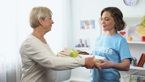 Voluntário novo que traz a bandeja do café da manhã para a senhora envelhecida, auxílio de apoio social vídeos de arquivo