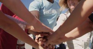 Voluntários que formam a pilha da mão na praia 4k vídeos de arquivo