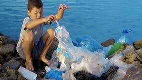 Volunt?rio da crian?a pequena que limpa a praia no oceano Conceito seguro da ecologia video estoque