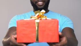 Voluntario afroamericano sonriente que lleva a cabo el giftbox de la cartulina, caridad de la ayuda metrajes