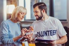 Voluntario amistoso calificado que sostiene una cacerola y que la explica foto de archivo libre de regalías