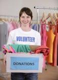 Voluntario con el rectángulo de la donación de la ropa Fotos de archivo