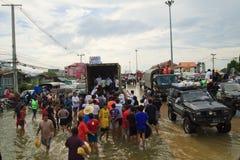 Voluntario dando un poco de alimento para las víctimas de inundación Fotografía de archivo