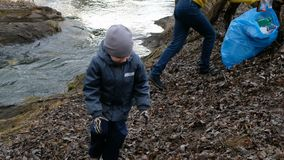 Voluntario de la mujer con su niño que limpia la basura por el río Concepto de la ecología y del ambiente almacen de video