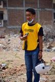 Voluntario del hombre joven que ayuda a gente después de desastre del terremoto Fotografía de archivo libre de regalías