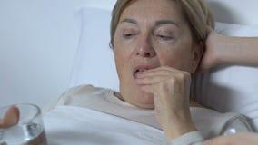 Voluntario del hospital que da la medicina paciente femenina con el vaso de agua, tratamiento almacen de video