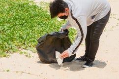 Voluntario del niño que recoge la basura en la playa hermosa en la playa de Karon fotografía de archivo