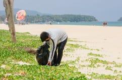 Voluntario del ni?o que recoge la basura en la playa hermosa en la playa de Karon fotos de archivo libres de regalías
