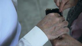 Voluntario del varón que pone billetes de banco euro en cartera femenina vieja, caridad y ayuda metrajes
