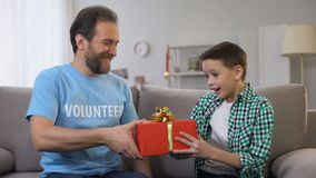 Voluntario joven que da el presente de cumpleaños del muchacho, adaptación social para los huérfanos, cuidado metrajes