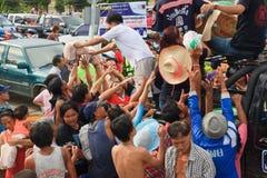 Voluntario tailandés que da un poco de pan y agua del alimento Imagenes de archivo