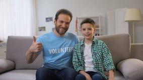 Voluntario y colegial de mediana edad sonrientes que empujan los pulgares-para arriba a la cámara, anuncio almacen de video
