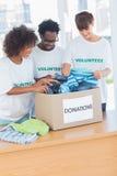 Voluntarios alegres que miran la ropa de una caja de las donaciones Fotografía de archivo