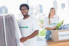 Voluntarios bonitos que sacan la ropa de una caja de la donación Fotografía de archivo