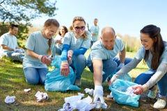 Voluntarios con los bolsos de basura que limpian área del parque fotos de archivo