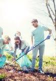 Voluntarios con los bolsos de basura que limpian área del parque fotografía de archivo
