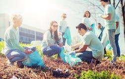 Voluntarios con los bolsos de basura que limpian área del parque imagen de archivo
