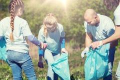 Voluntarios con los bolsos de basura que limpian área del parque foto de archivo